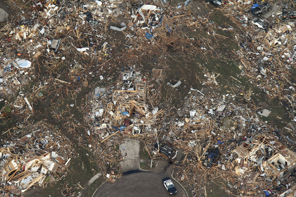 This aerial photo shows the remains of homes hit by a massive tornado in Moore, Okla., Monday May 20, 2013. A tornado roared through the Oklahoma City suburbs Monday, flattening entire neighborhoods, setting buildings on fire and landing a direct blow on an elementary school. (AP Photo/Steve Gooch) ORG XMIT: OKOKL138