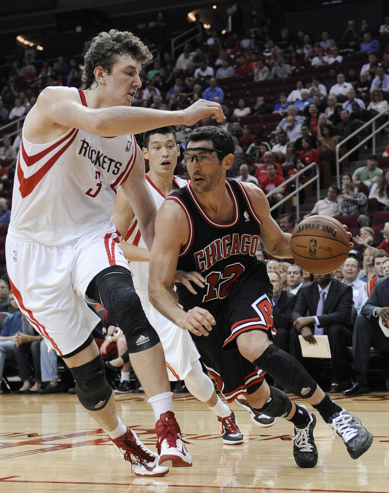 Photo -   Chicago Bulls' Kirk Hinrich (12) drives around Houston Rockets' Omer Asik (3) as Jeremy Lin watches from behind in the first half of an NBA basketball game Wednesday, Nov. 21, 2012, in Houston. (AP Photo/Pat Sullivan)