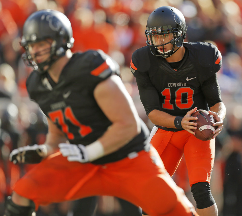 Oklahoma State\'s Clint Chelf (10) takes a snap in the third quarter near Parker Graham (71) during a college football game between the Oklahoma State University Cowboys (OSU) and the Kansas State University Wildcats (KSU) at Boone Pickens Stadium in Stillwater, Okla., Saturday, Oct. 5, 2013. OSU won, 33-29. Photo by Nate Billings, The Oklahoman