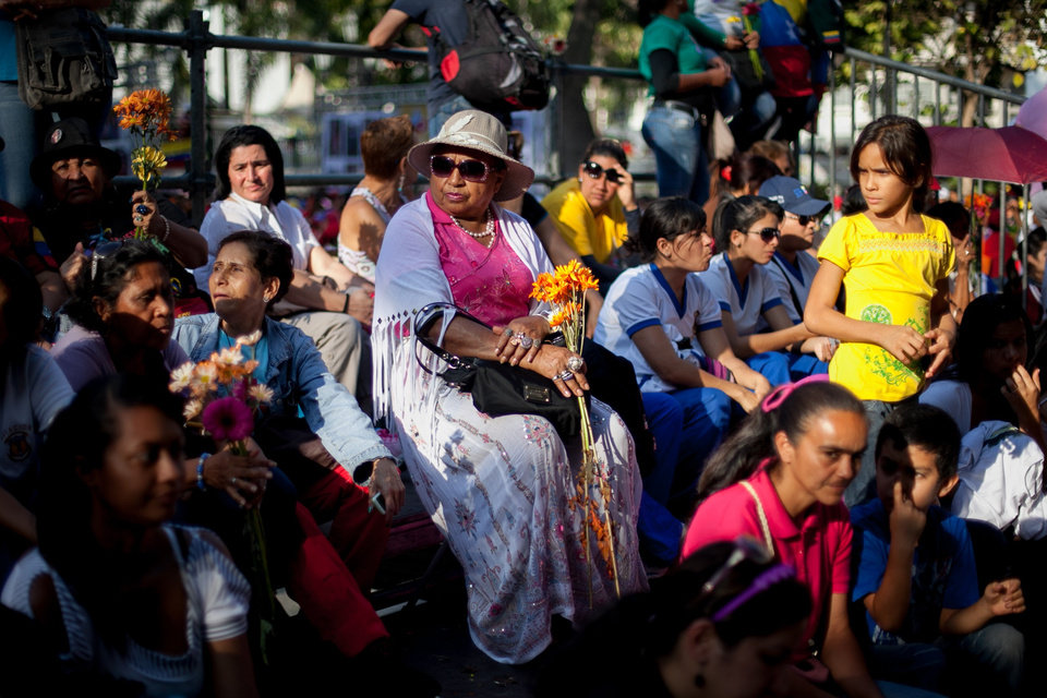 Photo - Women wait for the arrival of Venezuela's President Nicolas Maduro in Bolivar Square for a rally to commemorate International Women's Day in Caracas, Venezuela, Saturday, March 8, 2014. Maduro's government celebrated an Organization of American States declaration supporting its efforts to bring a solution to the country's worst political violence in years, calling it a diplomatic victory. The United States, Canada and Panama were the only nations to oppose the declaration. Meanwhile street protests continue almost daily while the opposition sits out a peace process it calls farcical. (AP Photo/Alejandro Cegarra)