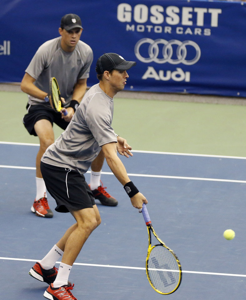 Photo - Mike Bryan hits a return to the doubles team of Raven Klaasen, of South Africa, and Eric Butorac in the finals at the U.S. National Indoor Tennis Championships Sunday, Feb. 16, 2014, in Memphis, Tenn. Klaasen and Butorac won 6-4, 6-4. (AP Photo/Rogelio V. Solis)