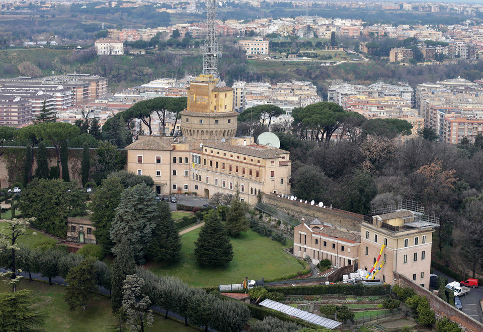 Photo - A view of the Mater Ecclesiae Monastery, right, next to the Tower of San Giovanni, inside the Vatican State where Pope Benedict XVI is expected to live after he resigns, on Tuesday, Feb. 12, 2013. For months, construction crews have been renovating a four-story building attached to a monastery on the northern edge of the Vatican gardens where nuns would live for a few years at a time in cloister. Only a handful of Vatican officials knew it would one day be Pope Benedict XVI's retirement home. On Tuesday, construction materials littered the front lawn of the house and plastic tubing snaked down from the top floor to a dump truck as the restoration deadline became ever more critical following Benedict's stunning announcement that he would resign Feb. 28 and live his remaining days in prayer. (AP Photo/Alessandra Tarantino)