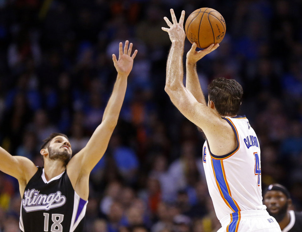Photo - Oklahoma City's Nick Collison (4) shoots a three-point basket as Sacramento's Omri Casspi (18) defends during the NBA basketball game between the Oklahoma City Thunder and Sacramento Kings at Chesapeake Energy Arena, Sunday, Nov. 9, 2014.  Photo by Sarah Phipps, The Oklahoman