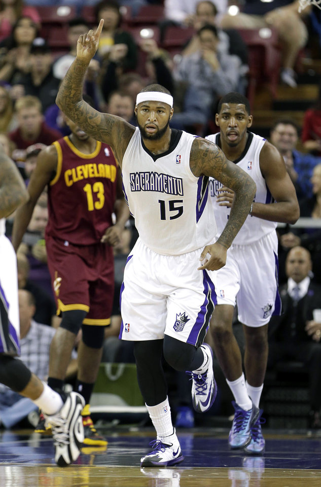 Photo - Sacramento Kings center DeMarcus Cousins gestures after scoring against the Cleveland Cavaliers during the first quarter of an NBA basketball game in Sacramento, Calif.,  Sunday, Jan. 12, 2014. (AP Photo/Rich Pedroncelli)