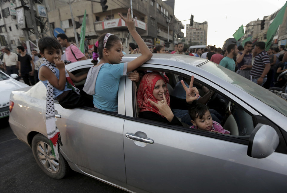 Photo - A Palestinian family flashes victory signs as they celebrate the cease-fire between Palestinians and Israelis at the main road in Gaza, in the northern Gaza Strip, Tuesday, Aug. 26, 2014.  Israel and Hamas agreed Tuesday to an open-ended cease-fire, halting a seven-week war that killed more than 2,200 people, the vast majority Palestinians, left tens of thousands in Gaza homeless and devastated entire neighborhoods in the blockaded territory.  (AP Photo/Adel Hana)