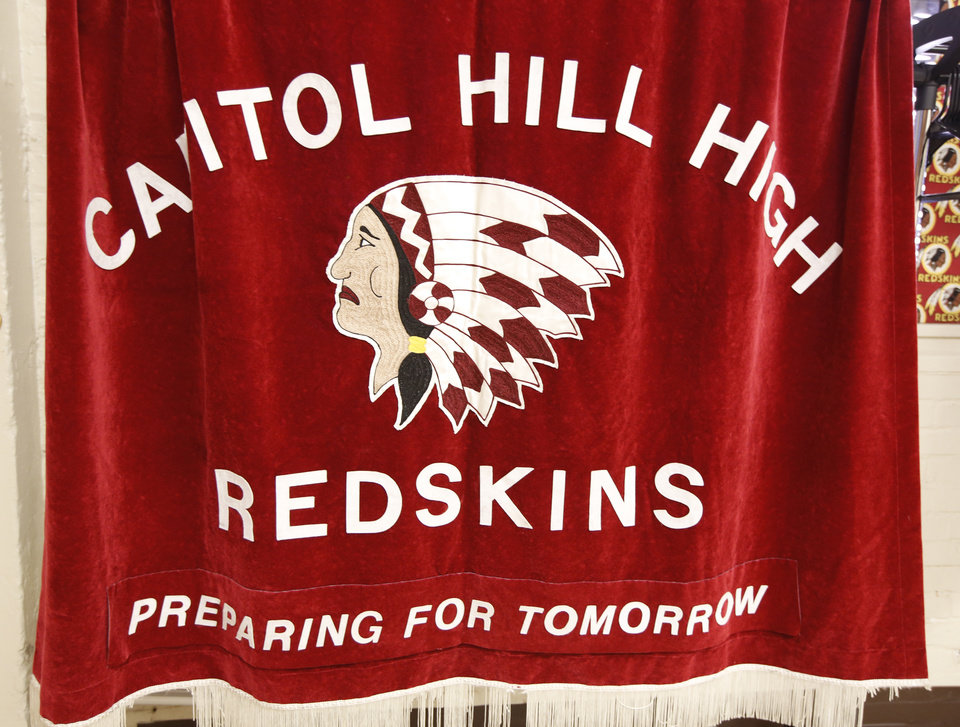 Photo - Left:  A Capitol Hill High School Redskins banner hangs in the alumni room at the school in Oklahoma City.  Steve Gooch -