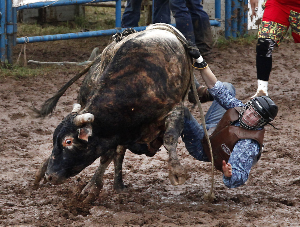 Photo - Charlie Romero, Edna, KS, tries to hang on and stay of the mud during Bull Riding at the International Youth Finals Rodeo in Shawnee at the Heart of Oklahoma Exposition Center, Wednesday, July 9, 2014. Photo by David McDaniel, The Oklahoman