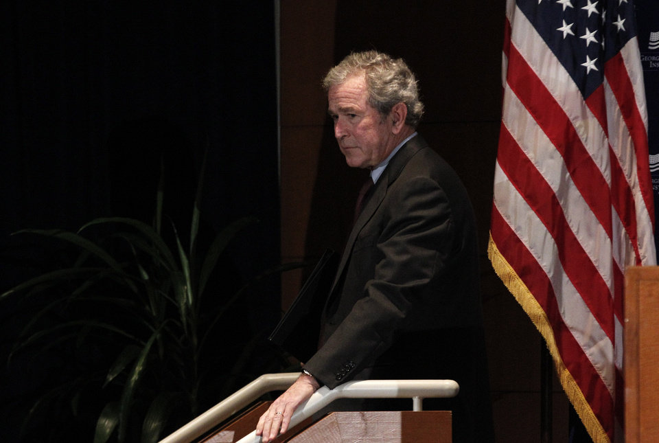Photo - Former President George W. Bush walks off the stage after giving opening remarks at the Federal Reserve Bank of Dallas for a conference titled