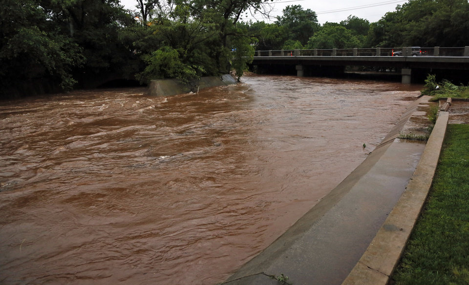 Photo - Water rushes down the Deep Fork River near Western Ave. after heavy rain during a thunder storm in Oklahoma City, Saturday, May 23, 2015. Photo by Nate Billings, The Oklahoman