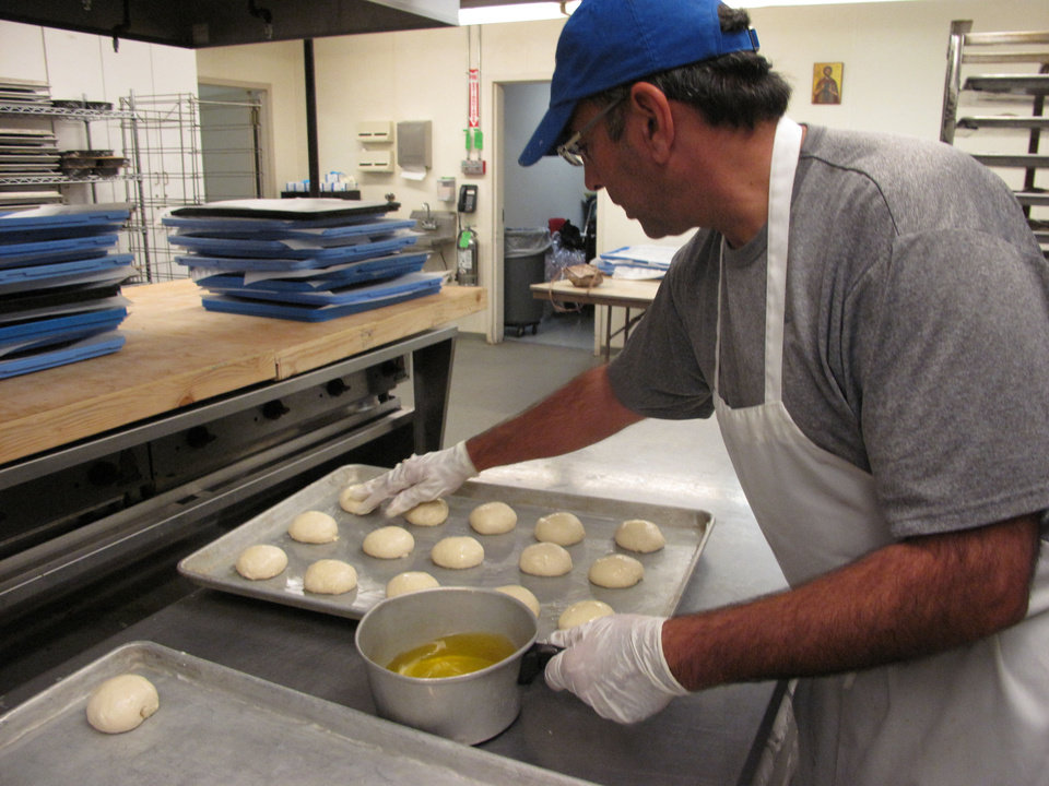 Photo - Volunteer Mike Sleem places bread dough in the form of rolls on a baking sheet at St. Elijah Antiochian Orthodox Christian Church in preparation of the church's annual food festival and holiday bake sale. Photos by Carla Hinton, The Oklahoman