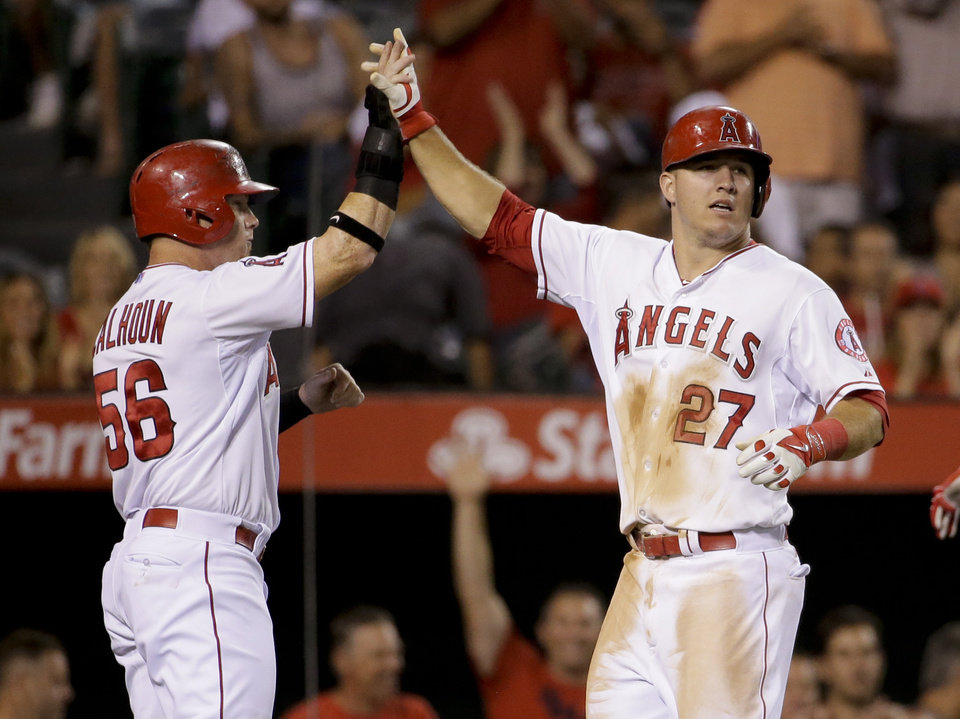 Photo - Los Angeles Angels' Mike Trout, right, celebrates with Kole Calhoun after scoring on a hit by Albert Pujols during the fourth inning of a baseball game against the Miami Marlins in Anaheim, Calif., Tuesday, Aug. 26, 2014. (AP Photo/Chris Carlson)