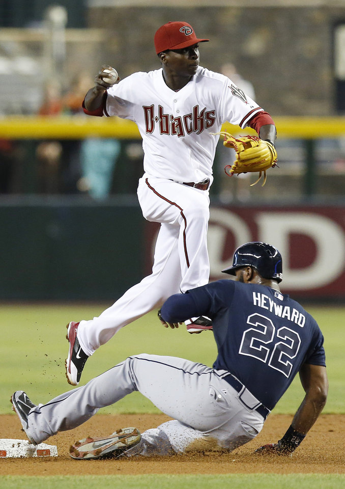 Photo - Arizona Diamondbacks' Didi Gregorius, top, forces out Atlanta Braves' Jason Heyward (22) at second base during the first inning of a baseball game on Friday, June 6, 2014, in Phoenix. (AP Photo/Ross D. Franklin)