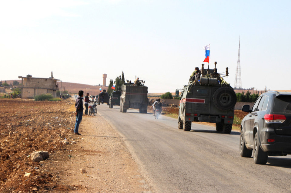 Photo -  Russian forces armored vehicles patrol the Syrian border in Kobani, Wednesday, Oct. 23, 2019. Russian military police began patrols on part of the Syrian border Wednesday, quickly moving to implement an accord with Turkey that divvies up control of northeastern Syria. (AP Photo)