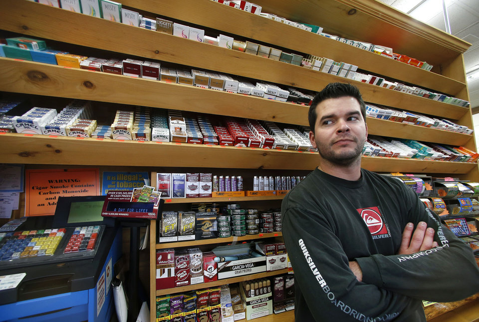 Photo - Brian Vincent poses in front of a large display of tobacco products at Vincent's Country Store in Westminster, Mass., Thursday, Nov. 6, 2014. Local officials are contemplating what could be a first: a blanket ban on all forms of tobacco and e-cigarettes, leaving some shop owners fuming. (AP Photo/Elise Amendola)