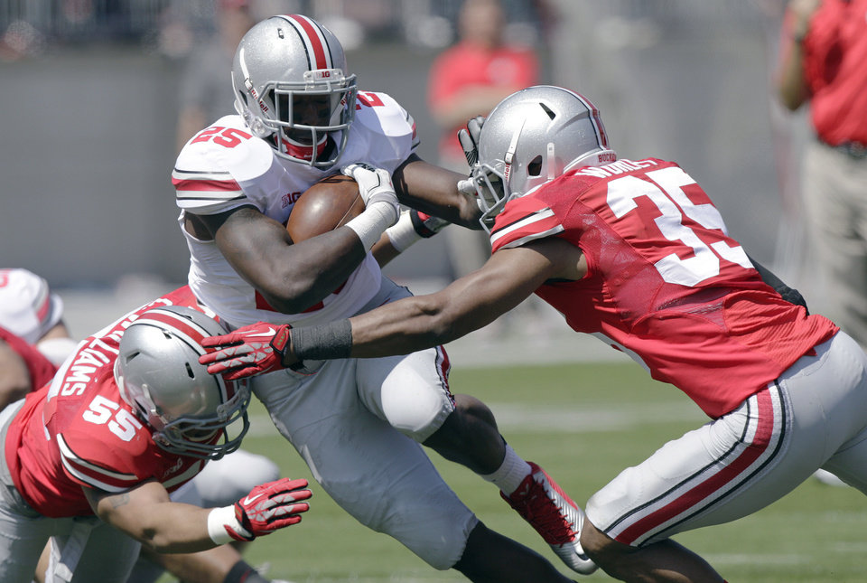 Photo - Ohio State running back Warren Ball, center, is tackled by linebacker Camren Williams, left, and linebacker Chris Worley during their spring NCAA college football game Saturday, April 12, 2014, in Columbus, Ohio. (AP Photo/Jay LaPrete)