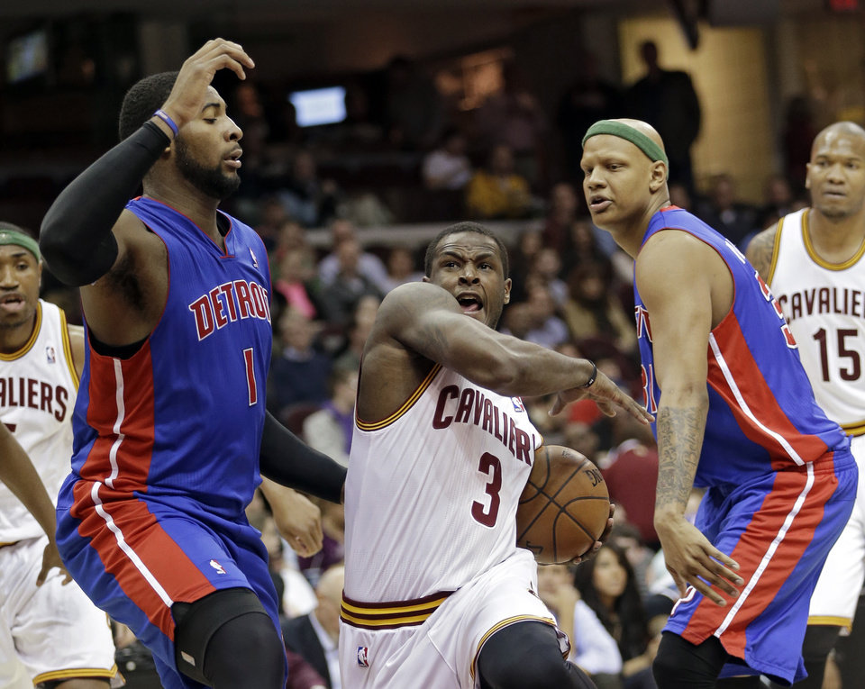 Photo - Cleveland Cavaliers' Dion Waiters (3) drives between Detroit Pistons' Andre Drummond (1) and Charlie Villanueva in the second quarer of an NBA basketball game on Wednesday, April 10, 2013, in Cleveland. (AP Photo/Mark Duncan)