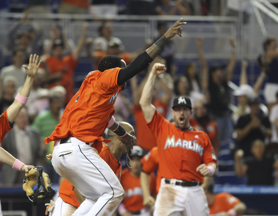 Photo -   Miami Marlins' Jose Reyes, front, Emilio Bonifacio and John Buck, right, celebrate after Giancario Stanton hit a game-winning grand slam against the New York Mets during the ninth inning of a baseball game in Miami, Sunday, May 13, 2012. The Marlins defeated the Mets 8-4. (AP Photo/J Pat Carter)