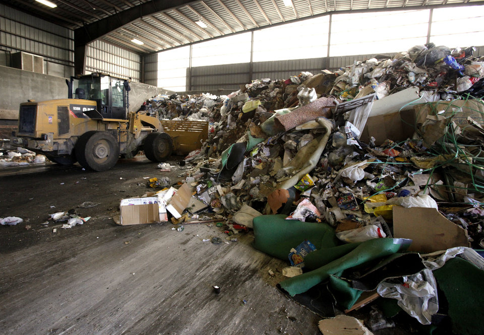 Photo - Norman sanitation crews dump a load of trash Tuesday at the city's transfer station.  PHOTO BY STEVE SISNEY, THE OKLAHOMAN