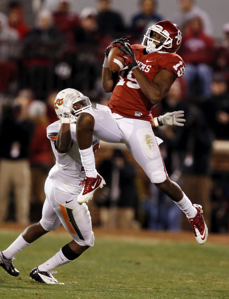 Photo - Oklahoma's Justin Brown (19) catches a pass in front of Oklahoma State's Brodrick Brown (19) during the second half of the Bedlam college football game in which  the University of Oklahoma Sooners (OU) defeated the Oklahoma State University Cowboys (OSU) 51-48 in overtime at Gaylord Family-Oklahoma Memorial Stadium in Norman, Okla., Saturday, Nov. 24, 2012. Photo by Steve Sisney, The Oklahoman