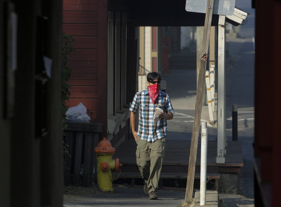 Alex Candia covers up to avoid breathing smoky air while walking along Highway 120 in Groveland, Calif. on Saturday, Aug. 24, 2013. The Rim Fire has scorched over 150 square miles of terrain. (AP Photo/San Francisco Chronicle, Paul Chinn)