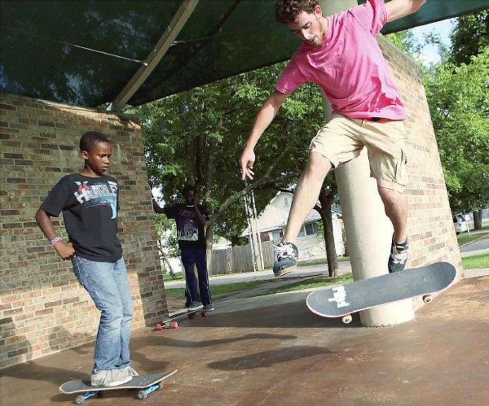Pete Miller, of Edmond, shows Aaron Ward, age 12, of Edmond, how to pull a trick during a skate demonstration outside the Edmond Public Library in Edmond on Monday, July 12, 2010. Photo by John Clanton, The Oklahoman ORG XMIT: KOD