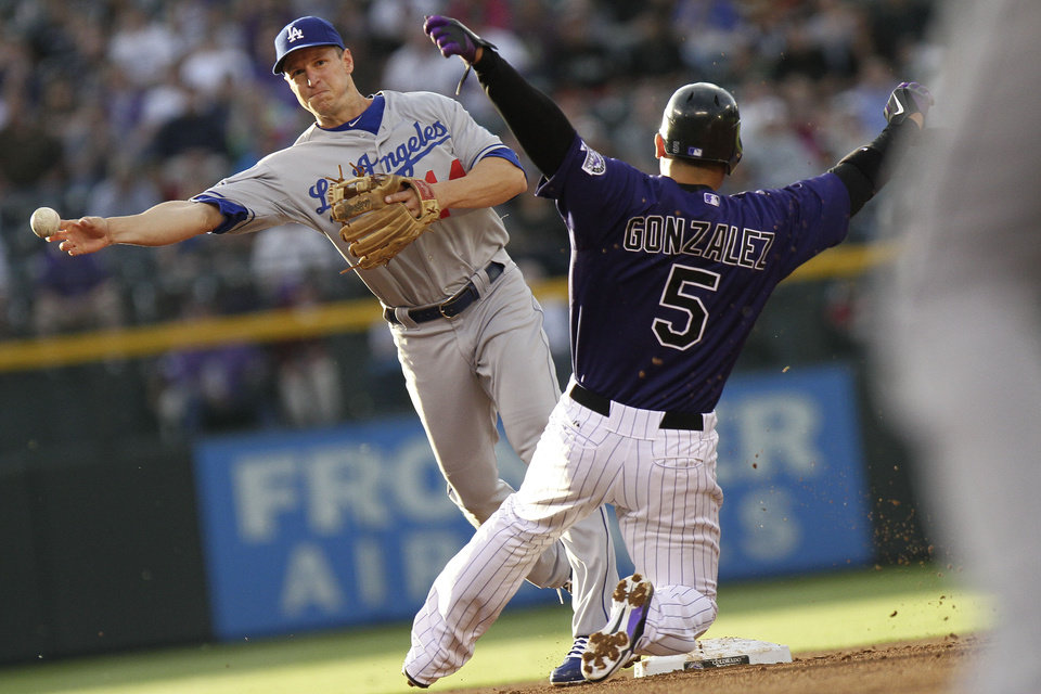 Photo -   Los Angeles Dodgers second baseman Mark Ellis (14) turns a double play after tagging out Colorado Rockies' Carlos Gonzalez (5) on Troy Tulowitzki grounder during the first inning of a baseball game Tuesday, May 1, 2012 in Denver. (AP Photo/Barry Gutierrez)
