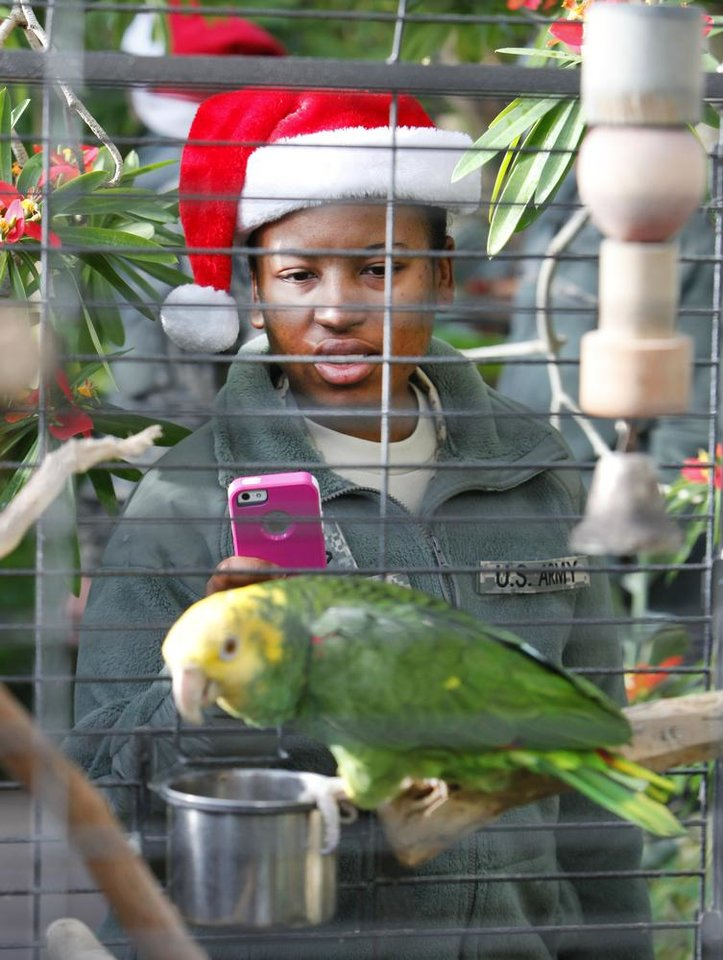New recruit Pfc Ashly Pierre take a photo of a parrot in the Crystal Bridge at the Myriad Gardens during Soldiers Day Out, Friday, December 21, 2012. Edmond/North OKC Blue Star Mothers will be taking the soldiers who can't go home for Christmas around the metro for a day of fun. Photo By David McDaniel/The Oklahoman