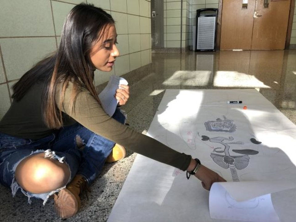 Photo -  Kaila Prisciliano, 16, works on a human anatomy assignment at Northwest Classen High School for her English language arts class on Nov. 15. Prisciliano, a sophomore, came to the U.S. in June from Chihuahua, Mexico. [Nuria Martinez-Keel/The Oklahoman]