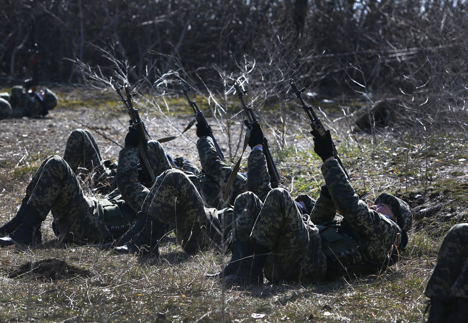 Photo - Ukrainian border guards perform an exercise in anti-air attack during training at a military camp in the village of Alekseyevka on the Ukrainian-Russian border, eastern Ukraine, Friday, March 21, 2014. Russian President Vladimir Putin has signed a resolution approved by parliament to annex Crimea. (AP Photo/Sergei Grits)