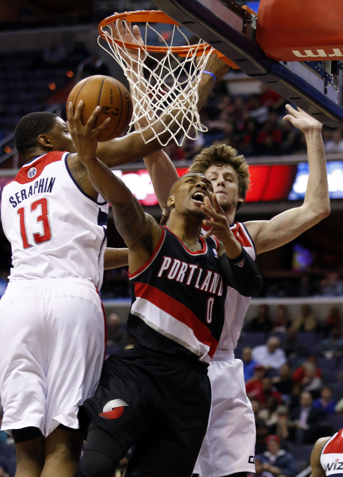 Photo - Portland Trail Blazers guard Damian Lillard (0) shoots as he is defended by Washington Wizards center Kevin Seraphin (13), of France, and forward Jan Vesely (24) in the first half of an NBA basketball game, Monday, Feb. 3, 2014, in Washington. (AP Photo/Alex Brandon)