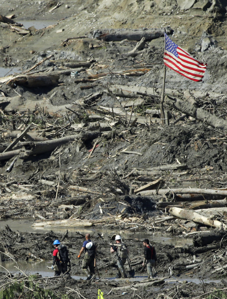 Photo - Workers carrying hand tools and shovels walk past a U.S. flag, Tuesday, April 1, 2014, near Darrington, Wash., in the debris field of the deadly mudslide that hit the community of Oso,Wash. on March 22, 2014. (AP Photo/Ted S. Warren)