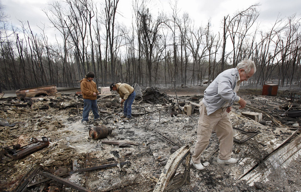 Photo - Rod Courtney steps through the rubble as he helps family members try to find salvageable remains from their house that was destroyed by wildfires on Friday, April 10, 2009, in Choctaw, Okla.  Photo by Chris Landsberger, The Oklahoman
