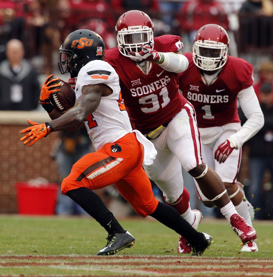 Photo - Cowboy's Tyreek Hill (24) tries to elude Sooner's Charles Tapper (91) during a Bedlam college football game between the University of Oklahoma Sooners (OU) and the Oklahoma State Cowboys (OSU) at Gaylord Family-Oklahoma Memorial Stadium in Norman, Okla., on Saturday, Dec. 6, 2014. Photo by Steve Sisney, The Oklahoman