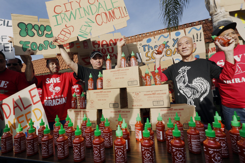Photo - Sriracha hot sauce founder David Tran, second from right, with his workers and supporters protest ahead of the city council meeting in Irwindale, Calif., Wednesday, April 23, 2014. The Irwindale City Council has declared that the factory that produces the popular Sriracha hot sauce is a public nuisance. (AP Photo/Damian Dovarganes)