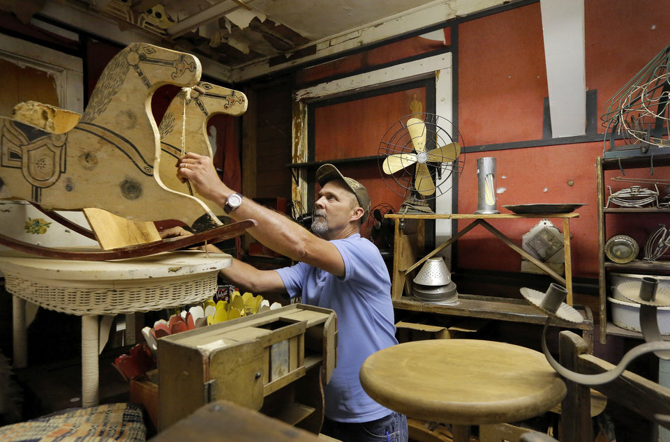 Photo -  Bert Hester looks at an old twin rocking horse inside his parents' antique shop May 28 in Choctaw. Photo by Jim Beckel, The Oklahoman   Jim Beckel -