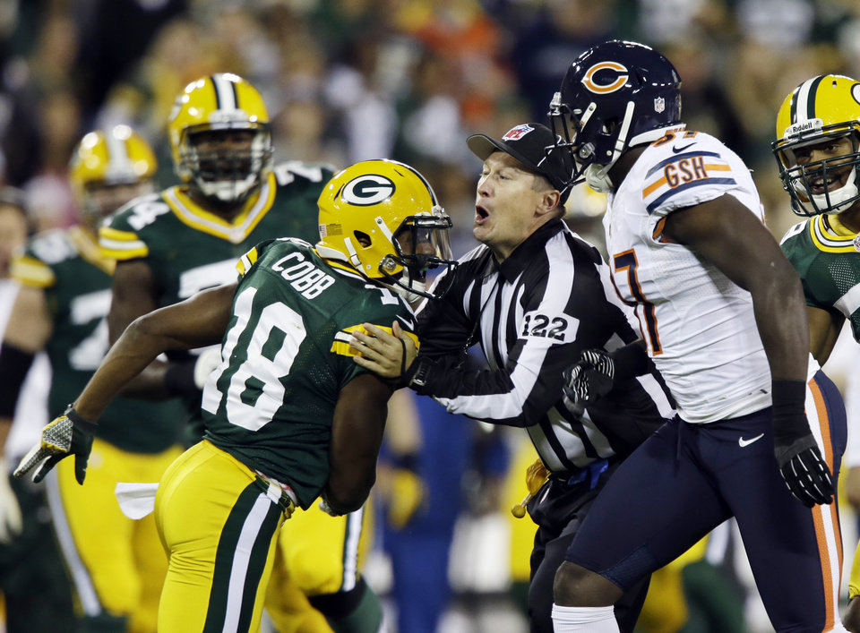 Photo -   Field judge George Trout gets between Green Bay Packers' Randall Cobb (18) and Chicago Bears' J.T. Thomas (97) during the first half of an NFL football game Thursday, Sept. 13, 2012, in Green Bay, Wis. (AP Photo/Jeffrey Phelps)