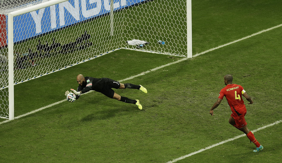 Photo - United States' goalkeeper Tim Howard makes a save as Belgium's Vincent Kompany, right, looks on during the World Cup round of 16 soccer match between Belgium and the USA at the Arena Fonte Nova in Salvador, Brazil, Tuesday, July 1, 2014. (AP Photo/Themba Hadebe)