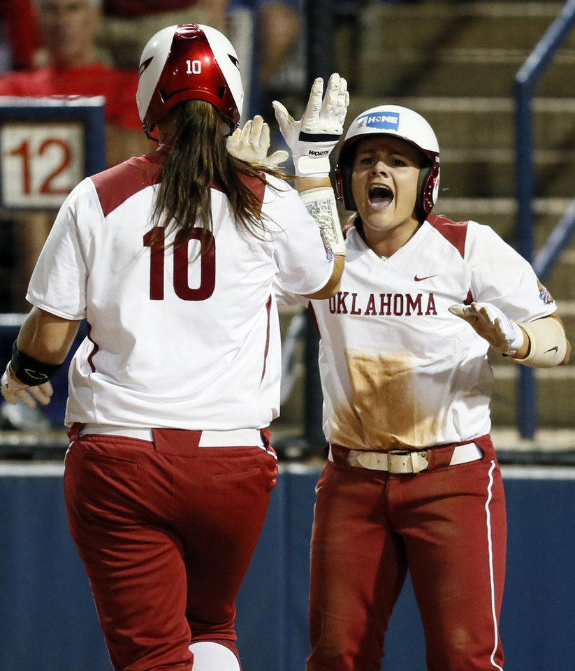 Photo - OU's Georgia Casey (42) greets Keilani Ricketts (10) at home plate as they both scored in the third inning during an NCAA softball game in the Women's College World Series between Oklahoma and Michigan at ASA Hall of Fame Stadium, Thursday, May 30, 2013. Photo by Nate Billings, The Oklahoman