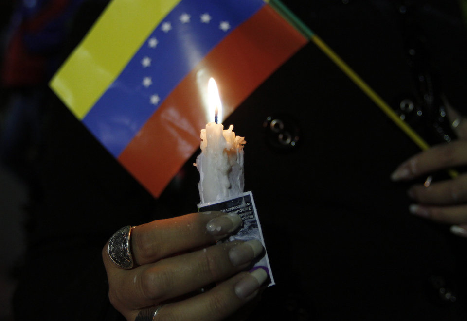 Photo - A person holds a candle and a Venezuelan flag during a vigil for Venezuela's President Hugo Chavez in La Paz, Bolivia, Monday Dec. 10, 2012. Chavez's cancer relapse and his sudden announcement that he will undergo a fourth cancer-related surgery in Cuba have thrown Venezuela's future into question. (AP Photo/Juan Karita)