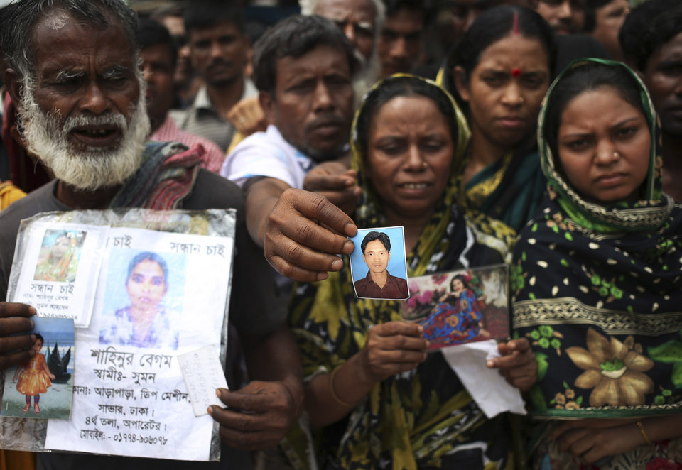 Photo - A man holds out a picture of his missing relative on Monday April 29, 2013 in Savar, near Dhaka, Bangladesh. Rescue workers in Bangladesh gave up hopes of finding any more survivors in the remains of a building that collapsed five days ago, and began using heavy machinery on Monday to dislodge the rubble and look for bodies - mostly of workers in garment factories there. At least 381 people were killed when the illegally constructed, 8-story Rana Plaza collapsed in a heap on Wednesday morning along with thousands of workers in the five garment factories in the building.(AP Photo/Wong Maye-E)