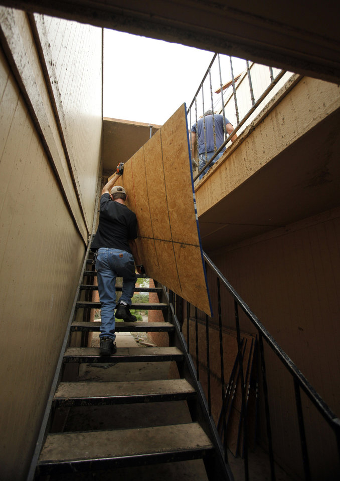 Photo - Workers at West Oaks Apartments move plywood up stairs to cover a roof blown off during Friday's tornado on Saturday, April 14, 2012, in Norman, Okla.  Photo by Steve Sisney, The Oklahoman