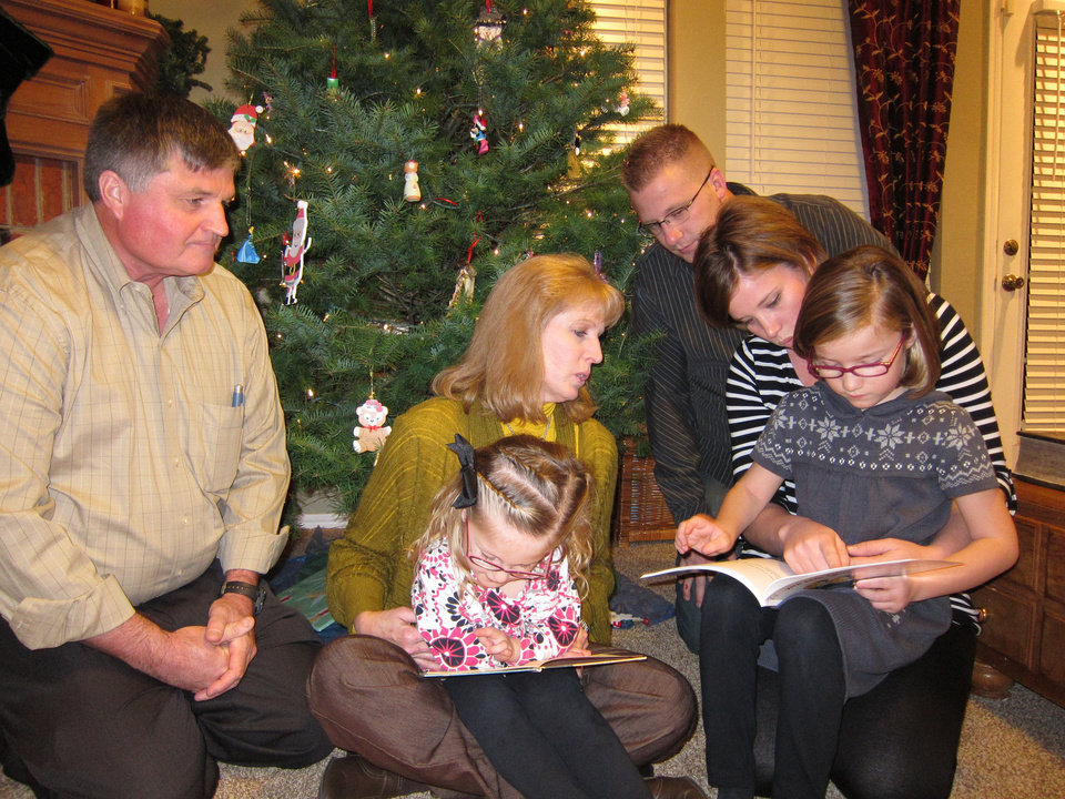 The Larsen family reads books together during a recent Christmas gathering. From left are: Brad and Jan Larsen, Brynlee Larsen, 4, Tyler and Jennifer Larsen and Makenna, 6. Photo by Carla Hinton <strong></strong>