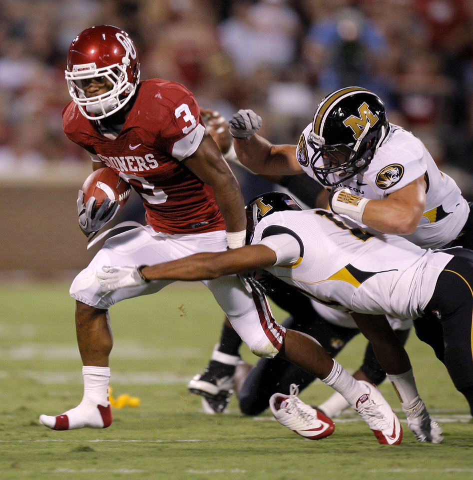 Oklahoma's Brennan Clay (3) runs past Missouri's Matt White, center, and Luke Lambert, right, during their game Saturday in Norman. Photo by Bryan Terry, The Oklahoman