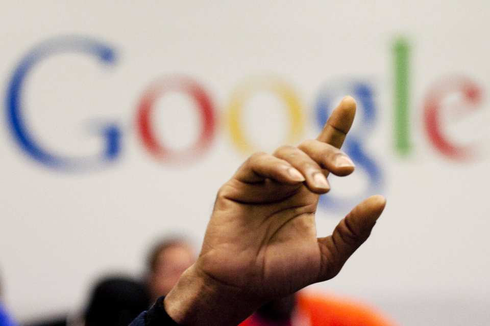 FILE - In this Oct. 17, 2012, file photo, a man raises his hand during at Google offices. Google's stock price topped $800 for the first time Tuesday, Feb. 20, 2013, amid renewed confidence in the company's ability to reap steadily higher profits from its dominance of Internet search and prominence in the increasingly important mobile device market.  (AP Photo/Mark Lennihan)