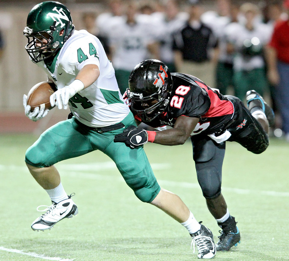 Photo - Norman North's Jaxon Uhles (left) tries to escape Westmoore's Archie Ocloolee during their game at Moore's stadium in Moore, Okla., on Thursday, Sept. 16, 2010. Photo by John Clanton, The Oklahoman