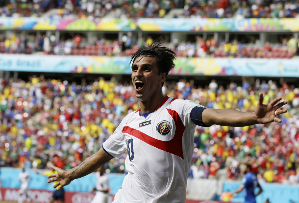 Photo - Costa Rica's Bryan Ruiz celebrates after scoring his side's first goal over Italy's goalkeeper Gianluigi Buffon during the group D World Cup soccer match between Italy and Costa Rica at the Arena Pernambuco in Recife, Brazil, Friday, June 20, 2014.  (AP Photo/Ricardo Mazalan)