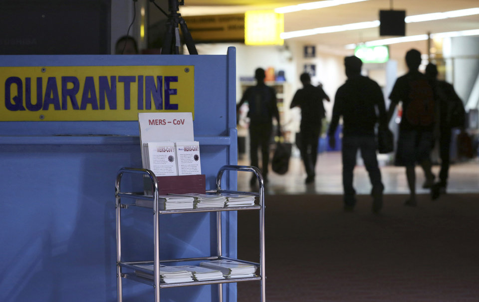 """Photo - FILE - In this Wednesday, April 16, 2014, file photo, passengers walk past the medical quarantine area showing information sheets for the Middle East respiratory syndrome coronavirus at the arrival section of Manila's International Airport in Paranaque, south of Manila. One expert says recent outbreaks of MERS in Saudi Arabia and the United Arab Emirates that led to more than 20 infections, many among health-care workers, """"have put us into uncharted territory.""""Saudi Arabia's King Abdullah sacked the country's health minister on Monday, April 21, 2014, amid a spike in deaths and infections from the virus known as the Middle East respiratory syndrome, or MERS. The official Saudi Press Agency carried the royal order that said Abdullah al-Rabiah was relieved of his post as Health Minister, and that Labor Minister Adel Faqih will temporarily take over the health minister's portfolio until a replacement is named. The statement said al-Rabiah is now adviser to the Royal Court.  (AP Photo/Aaron Favila, File)"""