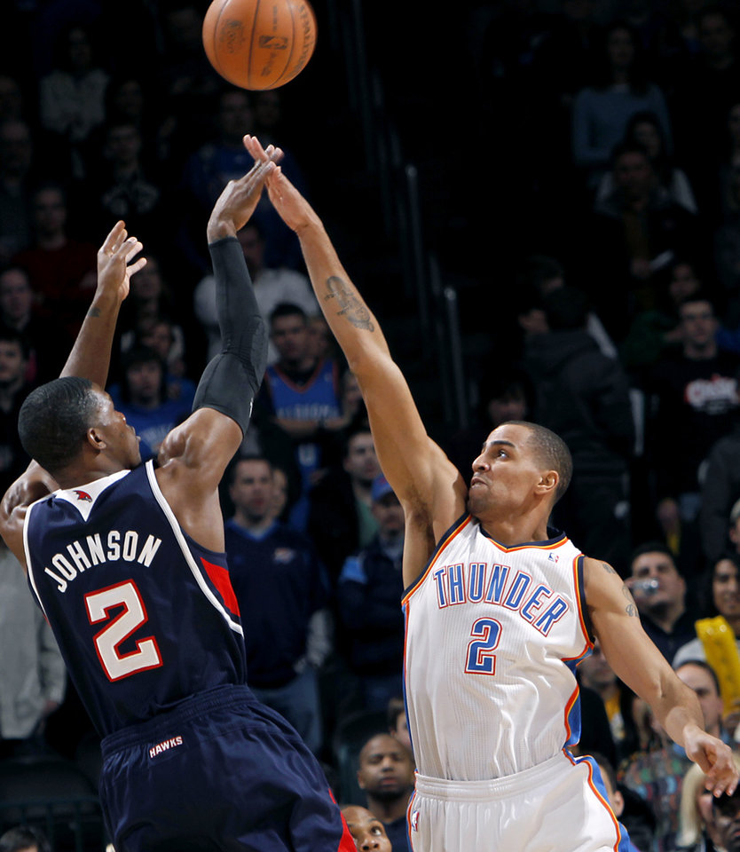 Photo - Oklahoma City's Thabo Sefolosha pressures a shot by Atlanta's Joe Johnson during their NBA basketball game at the OKC Arena in Oklahoma City on Friday, Dec. 31, 2010. Photo by John Clanton, The Oklahoman