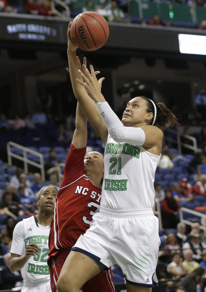 Photo - Notre Dame's Kayla McBride (21) drives past North Carolina State's Miah Spencer (3) during the second half of an NCAA college basketball semifinal game at the Atlantic Coast Conference tournament in Greensboro, N.C., Saturday, March 8, 2014. Notre Dame won 83-48. (AP Photo/Chuck Burton)