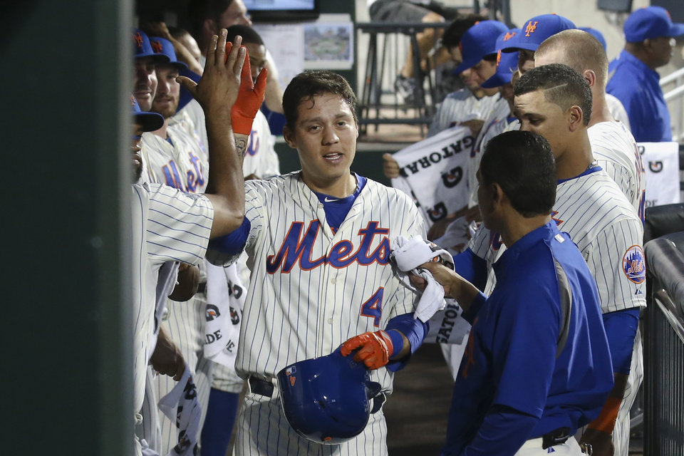 Photo - New York Mets' Wilmer Flores (4) celebrates in the dugout after hitting a solo home run in the second inning of a baseball game against the Atlanta Braves, Wednesday, Aug. 27, 2014, in New York. (AP Photo/John Minchillo)